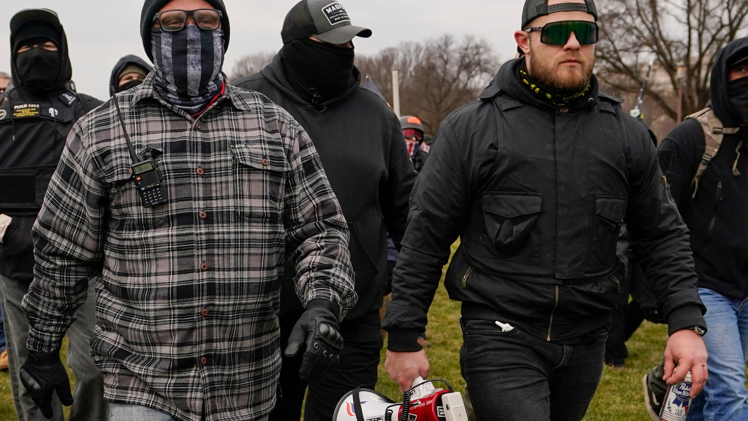 FILE - In this Jan. 6, 2021, file photo, Proud Boys members Joseph Biggs, left, and Ethan Nordean, right with megaphone, walk toward the U.S. Capitol in Washington. A federal judge has ordered Biggs and Nordean, two leaders of the far-right Proud Boys extremist group, to be arrested and jailed while awaiting trial on charges they planned and coordinated an attack on the U.S. Capitol to stop Congress from certifying President Joe Biden's electoral victory. The two had been free since their March 10 indictment, but U.S. District Judge Timothy Kelly concluded April 19, that the two men are dangerous and won't abide by release conditions. (AP Photo/Carolyn Kaster, File)