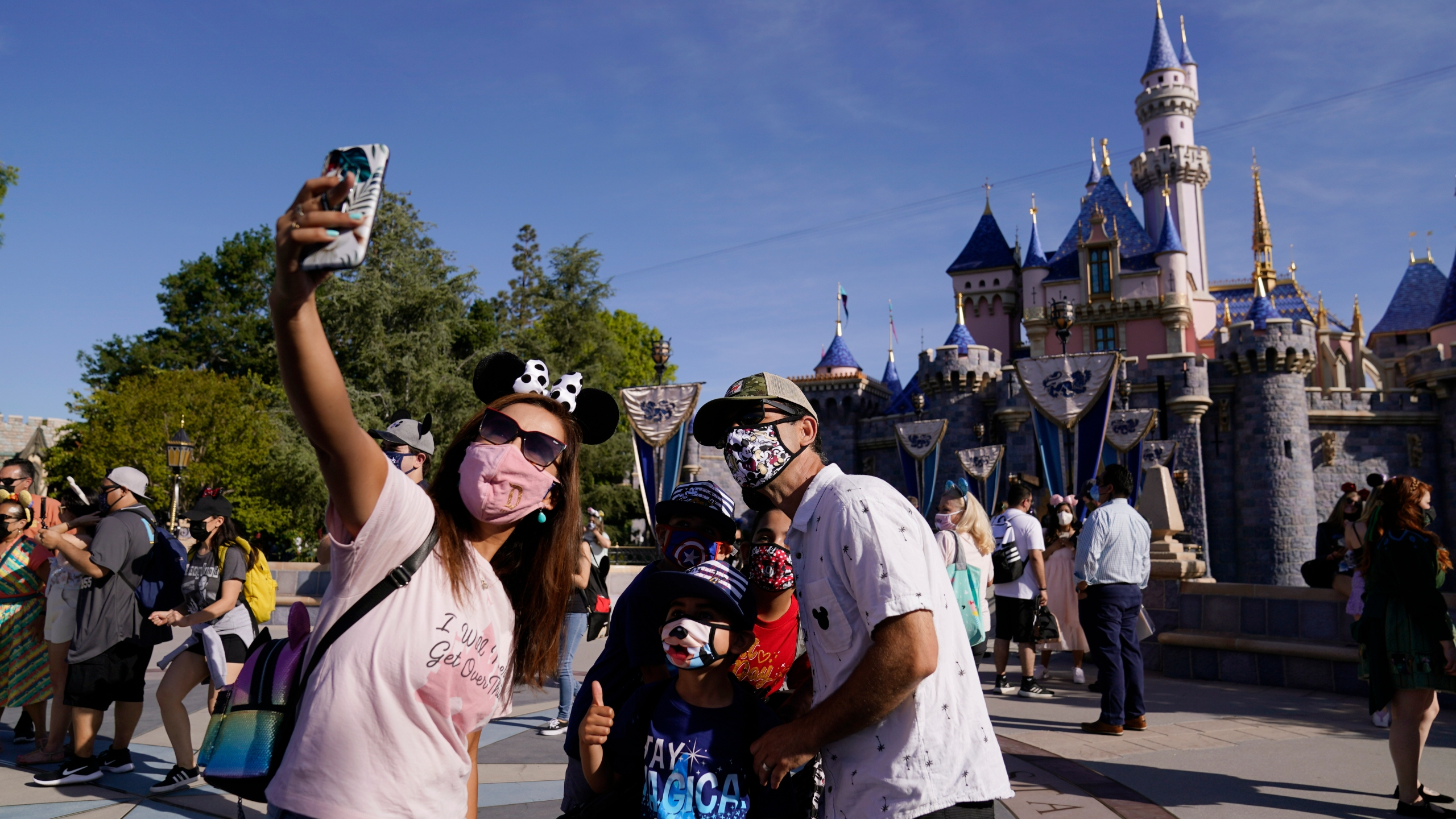 A family takes a photo in front of Sleeping Beauty's Castle at Disneyland in Anaheim, Calif., Friday, April 30, 2021. The iconic theme park in Southern California that was closed under the state's strict virus rules swung open its gates Friday and some visitors came in cheering and screaming with happiness. (AP Photo/Jae Hong)