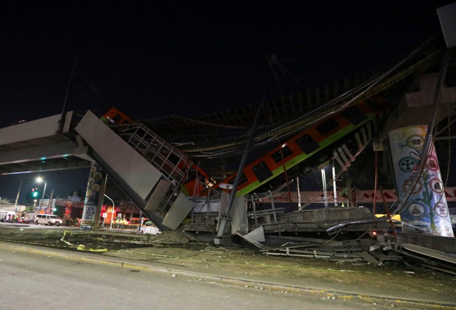 Mexico City's subway cars lay at an angle after a section of Line 12 of the subway collapsed in Mexico City, Tuesday, May 4, 2021. The section passing over a road in southern Mexico City collapsed Monday night, dropping a subway train, trapping cars and causing at least 50 injuries and several dead, authorities said. (AP Photo/Marco Ugarte)