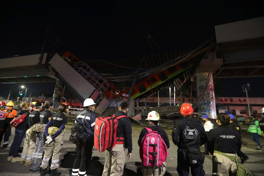 Rescue personnel stand in front of Mexico City subway cars laying at an angle after a section of Line 12 of the subway collapsed in Mexico City, Tuesday, May 4, 2021. The section passing over a road in southern Mexico City collapsed Monday night, dropping a subway train, trapping cars and causing at least 50 injuries and several dead, authorities said. (AP Photo/Marco Ugarte)