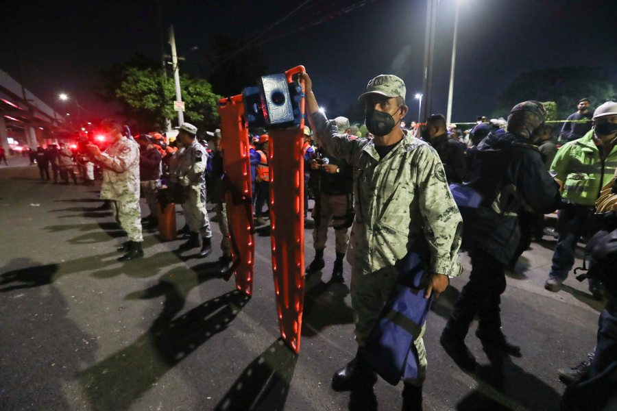 Mexico's army soldiers hold stretchers as they wait to help in the rescue efforts after a section of Line 12 of the subway collapsed in Mexico City, Tuesday, May 4, 2021. The section passing over a road in southern Mexico City collapsed Monday night, dropping a subway train, trapping cars and causing at least 50 injuries and several dead, authorities said. (AP Photo/Marco Ugarte)