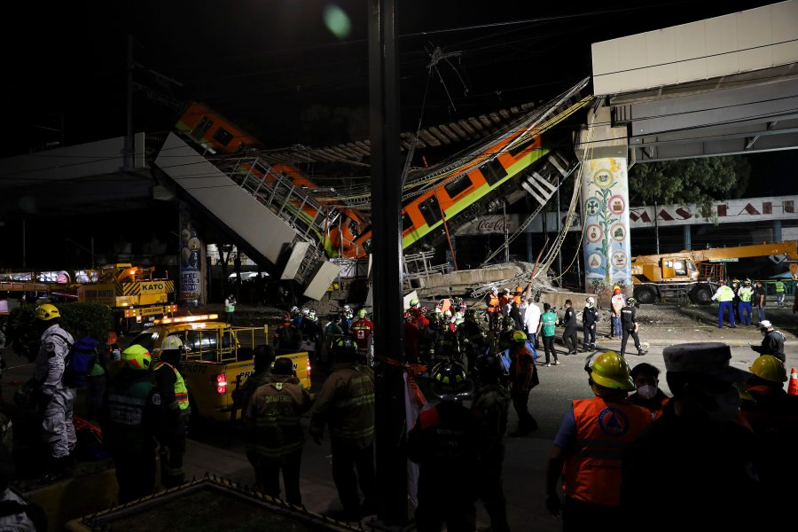 Mexico City's subway cars lay at an angle after a section of Line 12 of the subway collapsed in Mexico City, Tuesday, May 4, 2021. The section passing over a road in southern Mexico City collapsed Monday night, dropping a subway train, trapping cars, and causing at least 50 injuries and several dead, authorities said. (AP Photo/Marco Ugarte)