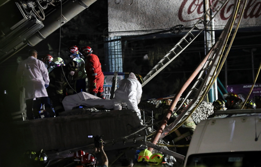 Mexican rescue personnel remove the body of a victim from a couple of subway cars that fell after a section of Line 12 of the subway collapsed in Mexico City, Monday, May 3, 2021. The section passing over a road in southern Mexico City collapsed Monday night, dropping a subway train, trapping cars, and causing at least 50 injuries and several dead, authorities said. (AP Photo/Marco Ugarte)