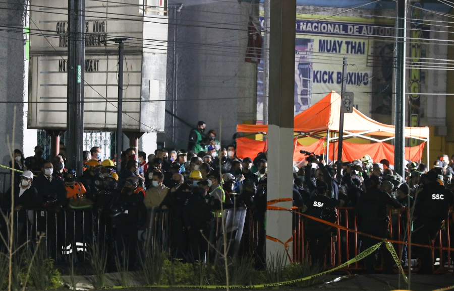 Media and onlookers are kept behind a police tape at the scene where subway cars fell after a section of Line 12 of the subway collapsed in Mexico City, Tuesday, May 4, 2021. The section passing over a road in southern Mexico City collapsed Monday night, dropping a subway train, trapping cars, and causing at least 50 injuries and several deaths, authorities said. (AP Photo/Marco Ugarte)