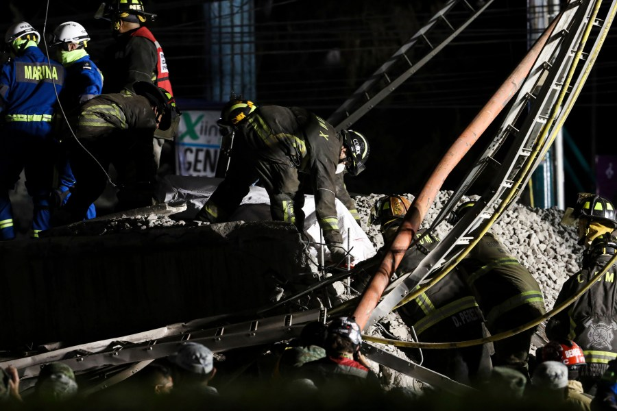 Rescue personnel retrieve bodies from the scene of an accident where subway cars fell after a section of Line 12 of the subway collapsed in Mexico City, Tuesday, May 4, 2021. The section passing over a road in southern Mexico City collapsed Monday night, dropping a subway train, trapping cars, and causing at least 50 injuries and several dead, authorities said. (AP Photo/Marco Ugarte)