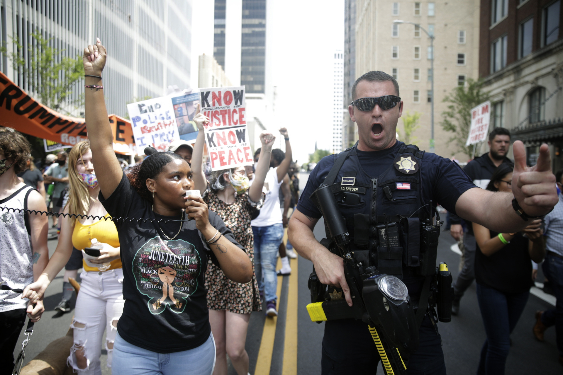 """FILE - In this Saturday, June 20, 2020 file photo, a Tulsa Police officer works near a Black Lives Matter event a few blocks away from the BOK Center before a rally by President Donald Trump in Tulsa, Okla. In a 2018 Gallup-Tulsa Citivoice Index poll designed to measure quality of life issues, only 18% of Black residents said they trust police a lot, compared to 49% of white residents, and 46% of Black Tulsans said they trust the Police Department """"not at all"""" or """"not much,"""" compared to 16% of whites. (Mike Simons/Tulsa World via AP, File)"""