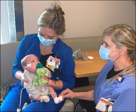 River looks up at one of his nurses, Hannah Privette, as he prepares to go home.