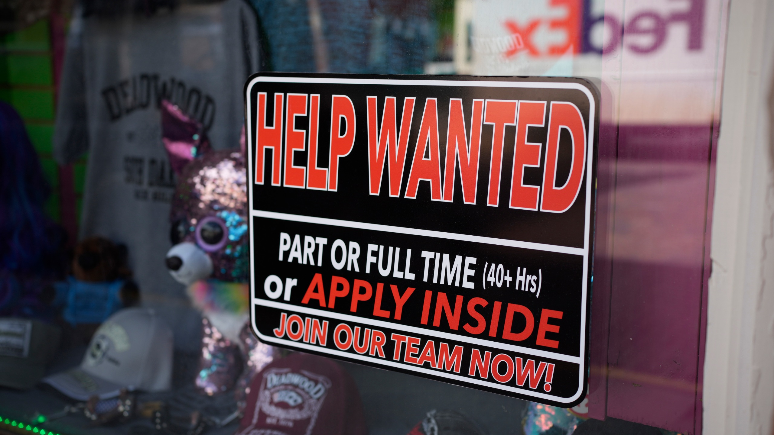 In this May 26, 2021 photo, a sign for workers hangs in the window of a shop along Main Street in Deadwood, S.D. U.S. employers added 559,000 jobs in May, an improvement from April's sluggish gain but still evidence that many companies are struggling to find enough workers as the economy rapidly recovers from the pandemic recession. (AP Photo/David Zalubowski)