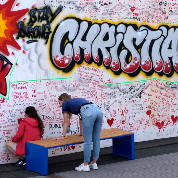 People leave well wishes at a graffiti for Danish player Christian Eriksen on a wall at the fanzone in Copenhagen, Denmark, Monday, June 14, 2021. Eriksen remains in hospital after he collapsed on the pitch during the European Championship game against Finland on Saturday and needed CPR from medical staff before regaining consciousness. (AP Photo/Martin Meissner)