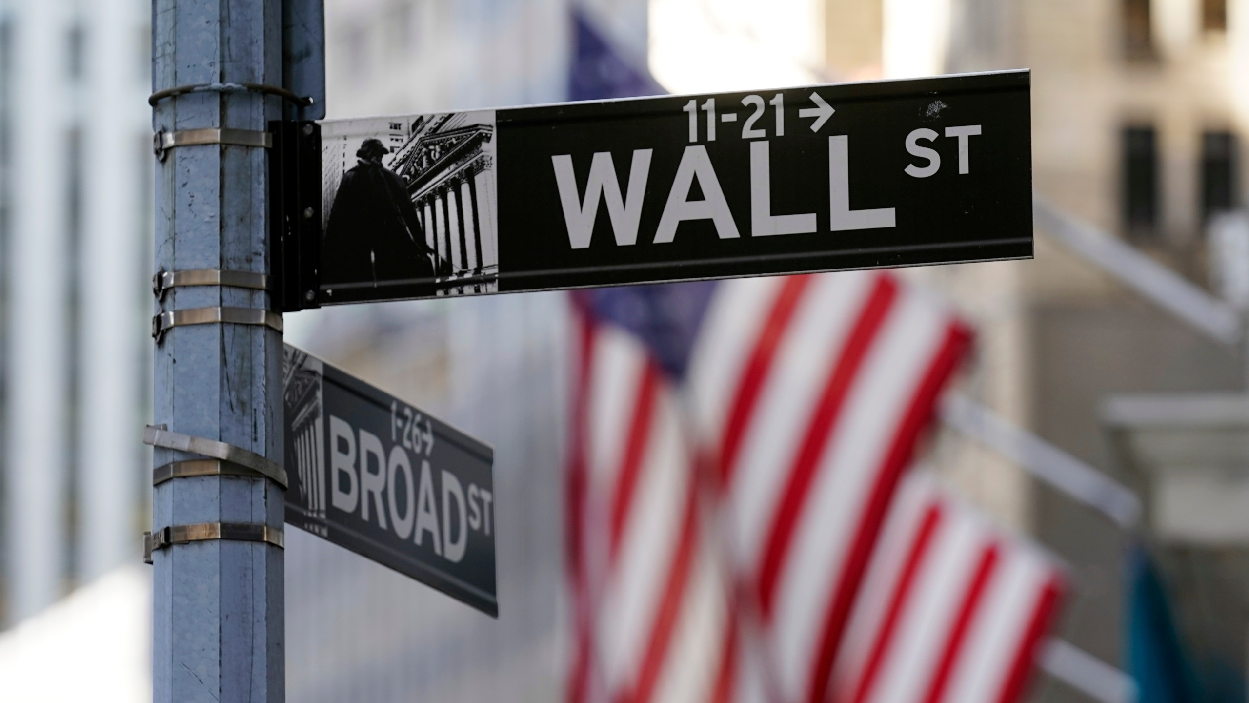 Flags adorn the facade of the New York Stock Exchange, Wednesday, June 16, 2021. Stocks are off to a mixed start on Wall Street Wednesday as traders wait for the latest decision on interest rates from the Federal Reserve. (AP Photo/Richard Drew)