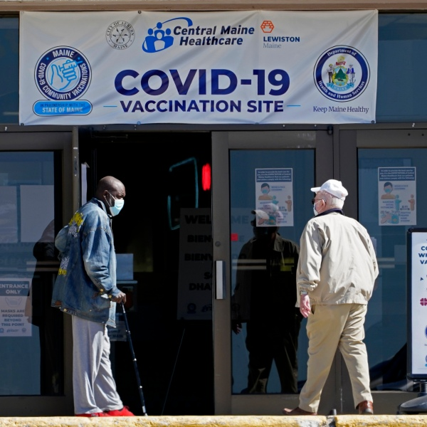 FILE - In this May 12, 2021, file photo, one man holds the door for another as they arrive at a COVID-19 vaccination clinic at the Auburn Mall in Auburn, Maine. As cases fall and states reopen, the potential final stage in the U.S. campaign to vanquish COVID-19 is turning into a slog, with a worrisome variant gaining a bigger foothold and lotteries and other inducements failing to persuade some Americans to get vaccinated. Maine and other states are convening focus groups to better understand who is declining to get vaccinated, why, and how they could be persuaded that vaccinating is the right choice. (AP Photo/Robert F. Bukaty)