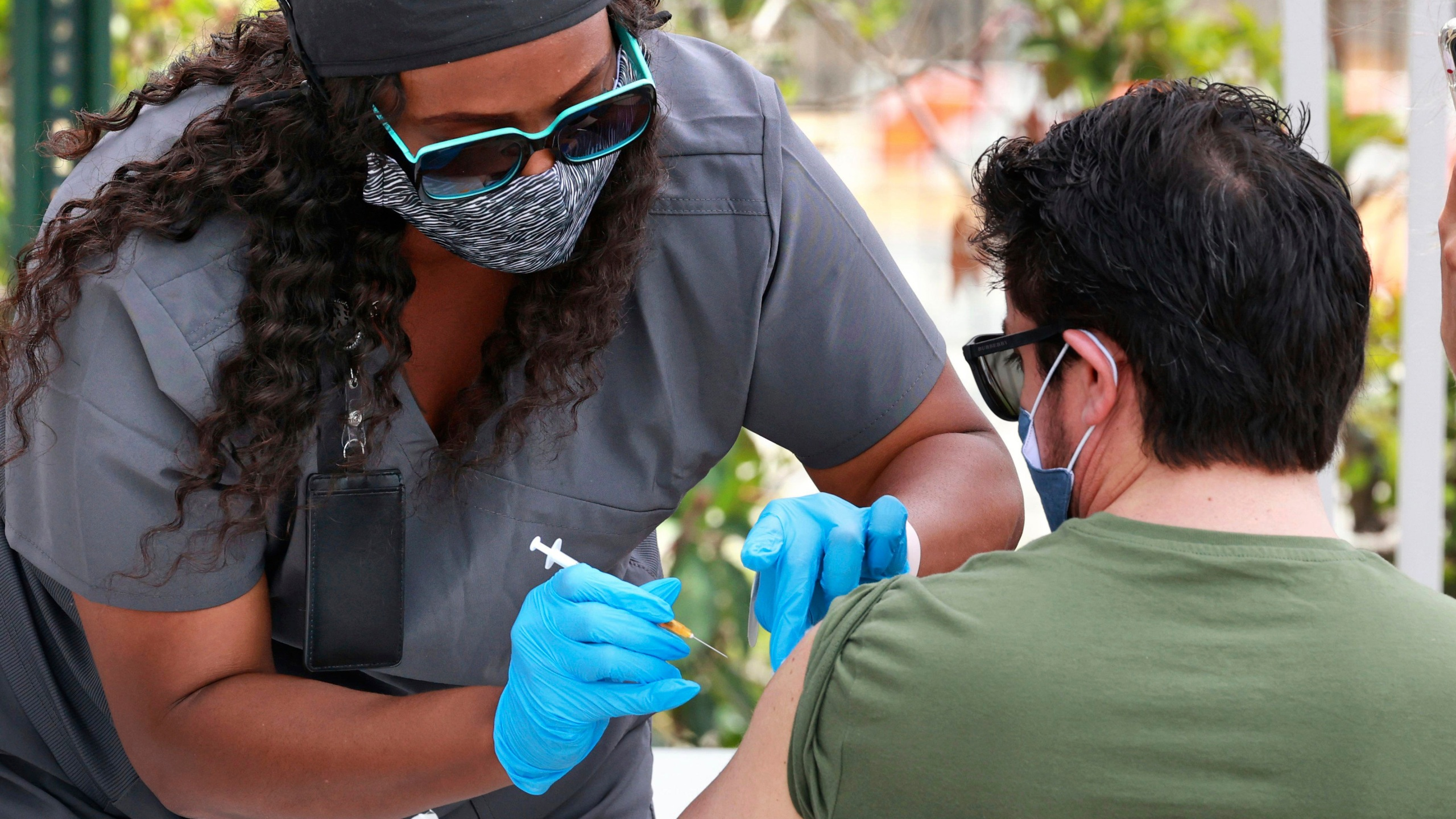FILE - In this June 17, 2021, file photo, an Orange County resident receives the COVID-19 vaccine at the Florida Division of Emergency Management mobile vaccination site at Camping World Stadium in Orlando, Fla. COVID-19 deaths in the U.S. have dipped below 300 a day for the first time since the early days of the disaster in March 2020, while the number of Americans fully vaccinated has reached about 150 million. (Joe Burbank/Orlando Sentinel via AP, File)