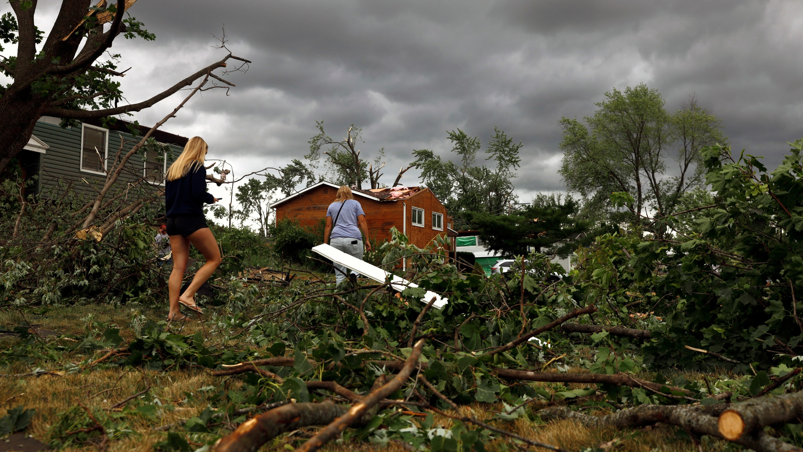 Residents walk past damaged houses and fallen trees after a tornado passed through the area on Monday, June 21, 2021 in Woodridge, Ill. (AP Photo/Shafkat Anowar)