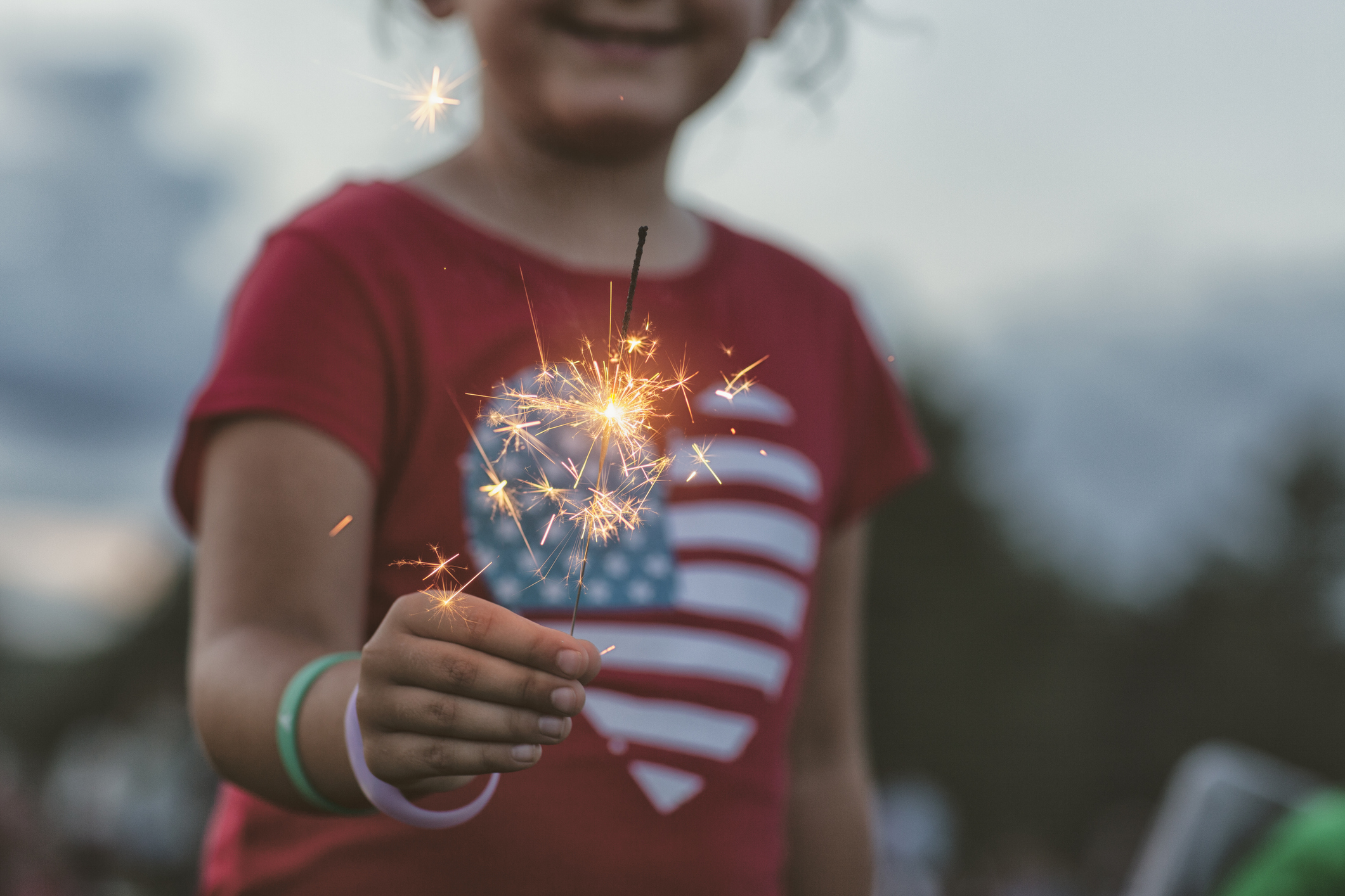 Girl holding lit sparkler (Getty Images)