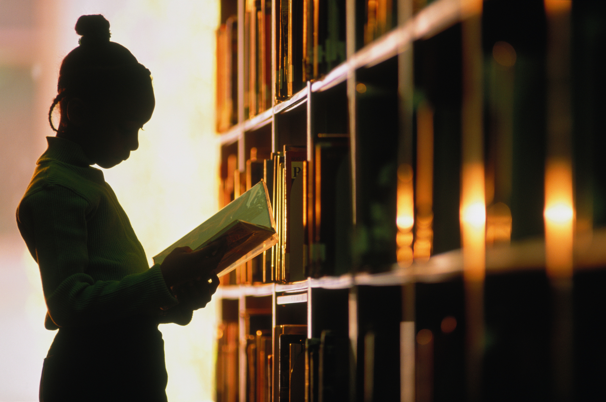 Girl looking at book in library, silhouette (Getty)