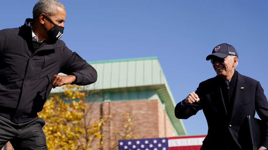 FILE - In this Oct. 31, 2020, file photo Democratic presidential candidate former Vice President Joe Biden, right, and former President Barack Obama greet each other with an air elbow bump, at the conclusion of rally at Northwestern High School in Flint, Mich. (AP Photo/Andrew Harnik, File)