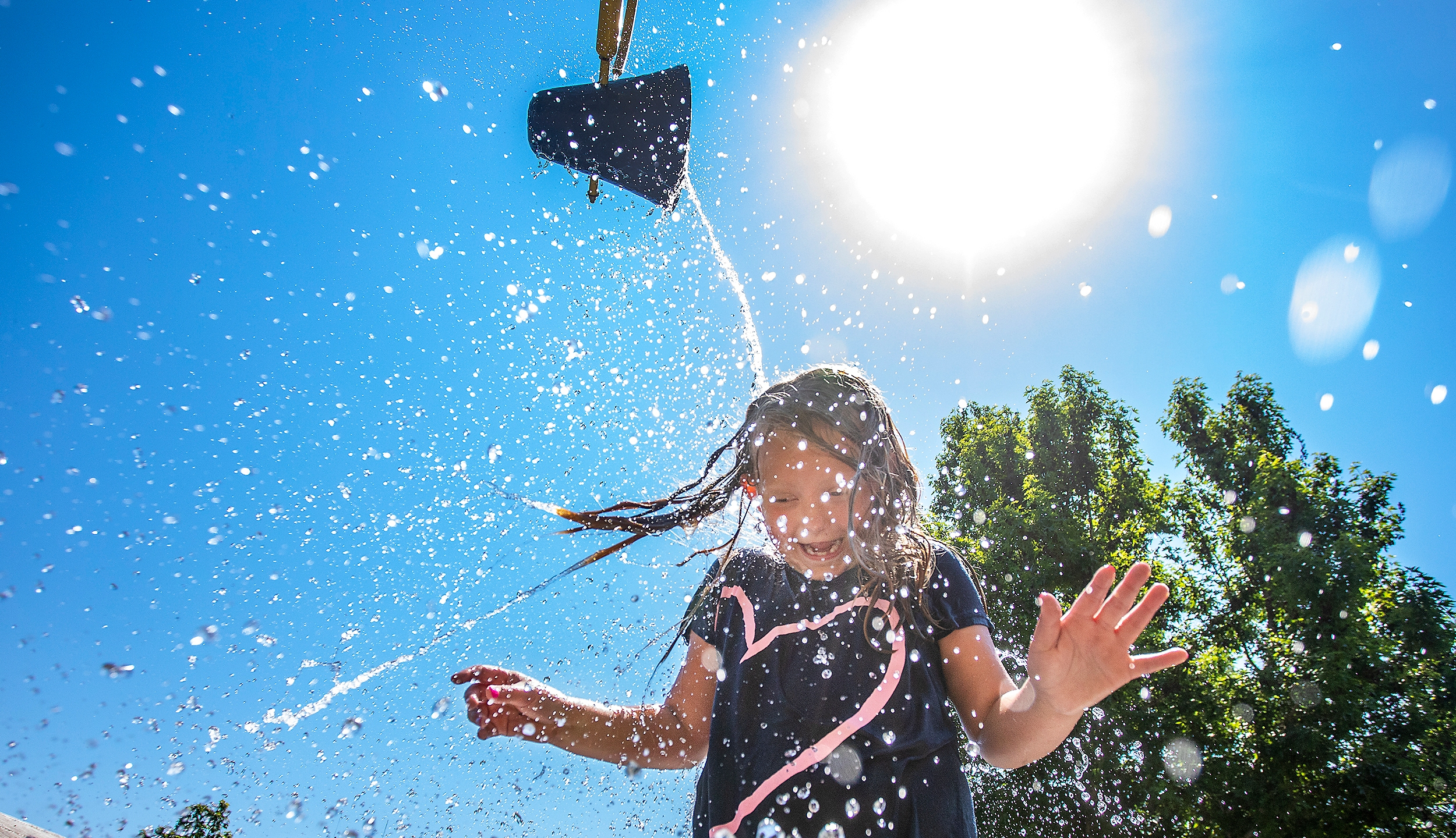 Water comes crashing down from a bucket directly on top of Jaecee Adams, 7, of Orofino, as she plays at the Orofino Splash Pad in Orofino, Idaho on Wednesday, June 30, 2021. (August Frank/The Lewiston Tribune via AP)