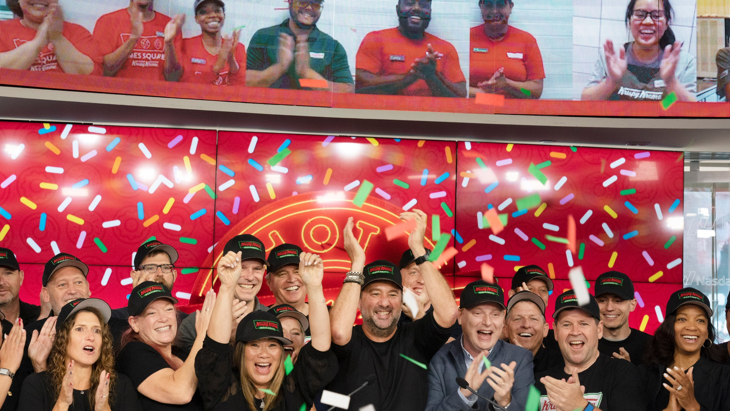 Krispy Kreme CEO Mike Tattersfield, center, applauds during the company's IPO at the Nasdaq Opening Bell, Thursday, July 1, 2021 in New York. The Charlotte, North Carolina-based company, known for its glazed doughnuts, priced its initial public offering of 29.4 million shares at $17 a piece. That's well below the $21 to $24 it was seeking. It raised $500 million and plans to use proceeds to pay down debt. (AP Photo/Mark Lennihan)