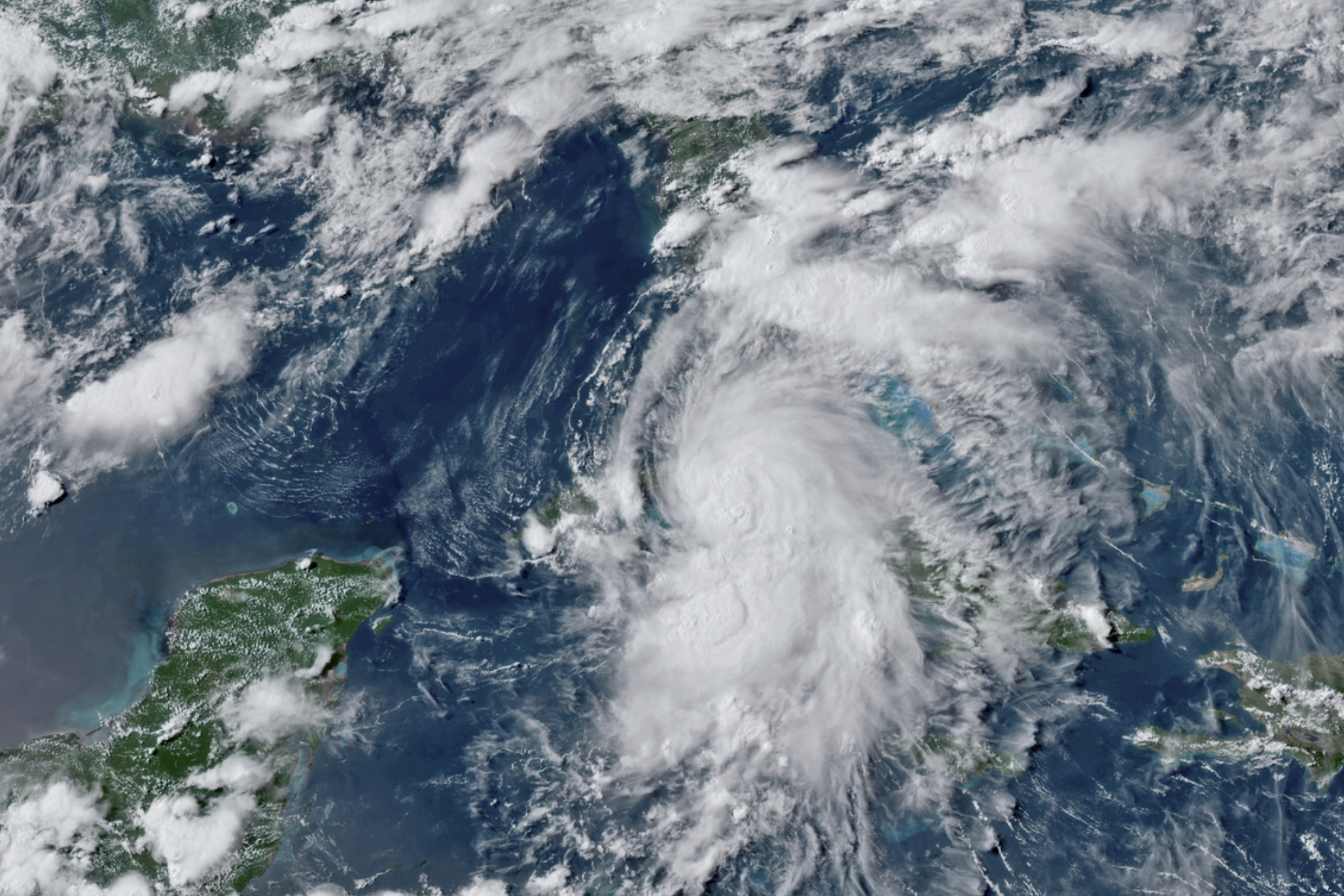This GOES-16 GeoColor satellite image taken Monday, July 5, 2021, at 4:50 p.m. EDT, and provided by NOAA, shows Tropical Storm Elsa over western Cuba with strong rain and winds. Forecasters say it will move on to the Florida Keys on Tuesday and Florida's central Gulf coast by Wednesday. The storm is moving over mainly rural areas to the east of Havana on Monday after making landfall near Cienega de Zapata, a natural park with few inhabitants. (NOAA via AP)