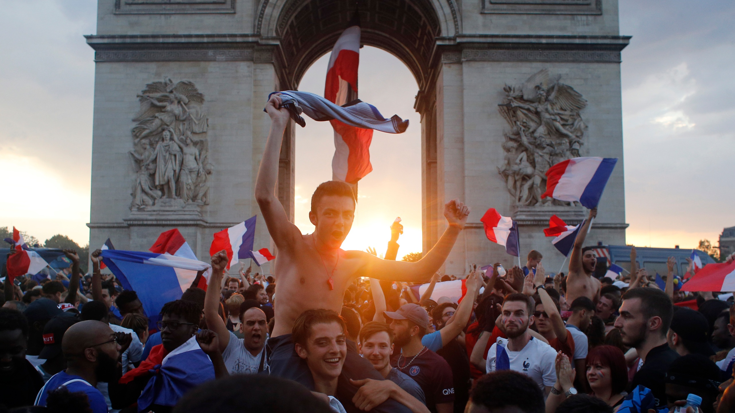 FILE - In this Sunday, July 15, 2018 file photo, people gather around the Arc de Triomphe in Paris, to celebrate France's World Cup victory over Croatia. On Friday, July 23, 2021, The Associated Press reported on a photo of a blond woman with a flag atop the Arc de Triomphe circulating online, incorrectly asserting it shows recent protests in Paris over the government's latest coronavirus measures. But the photo shows celebrations in Paris in July 2018 after France won the World Cup, not a recent protest. (AP Photo/Thibault Camus, File)