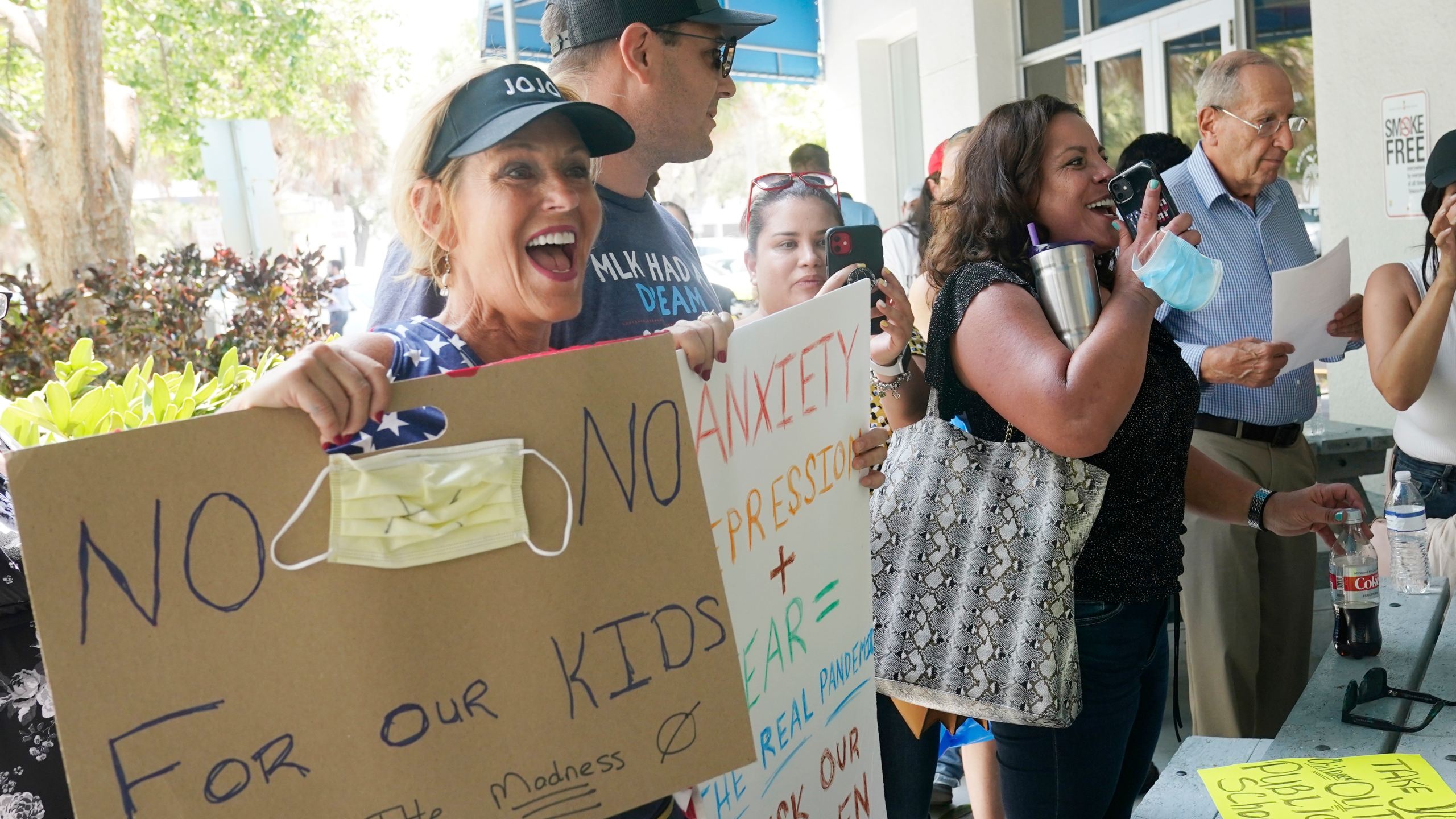 Joann Marcus of Fort Lauderdale, left, cheers as she listens to the Broward School Board's emergency meeting, Wednesday, July 28, 2021, in Fort Lauderdale, Fla. A small but vocal group spoke vehemently against masks, saying their personal rights were being eroded and their children were suffering socially. (AP Photo/Marta Lavandier)