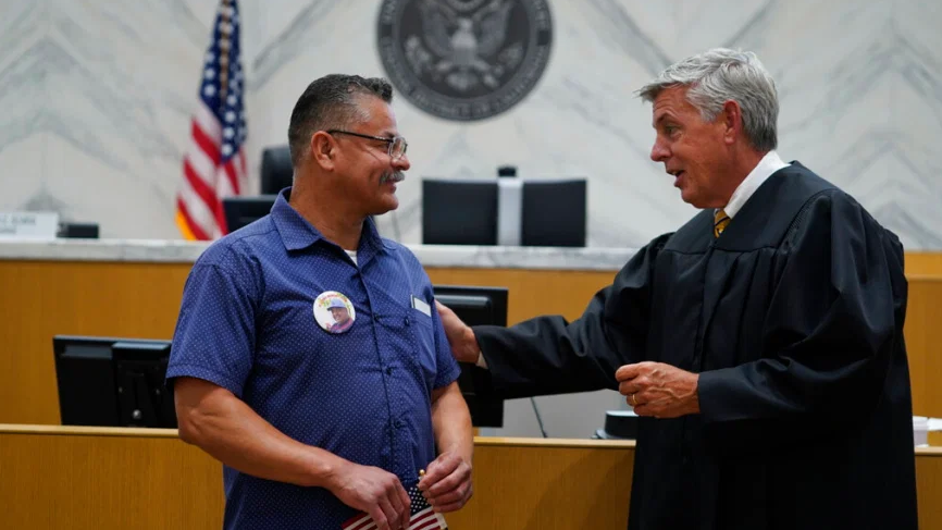 Judge Mark C. Scarsi, right, thanks U.S. Marine Corps Hector Ocegueda for his military service after administering the citizenship oath in a federal courtroom in Los Angeles Friday, July 9, 2021. Ocegueda was brought to the United States from Mexico by his parents and grew up in the Southern California city of Artesia. He served in the Marine Corps from 1987 to 1991 and spent four more years in the reserves before he was honorably discharged. He got married, had two daughters and obtained a green card through his wife. (AP Photo/Damian Dovarganes)