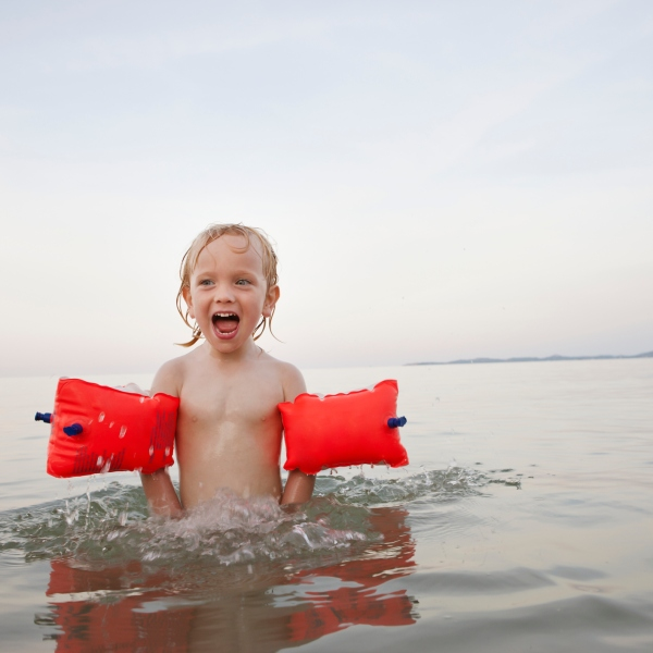 Boy (7-9) with water wings swimming in lake (Getty)