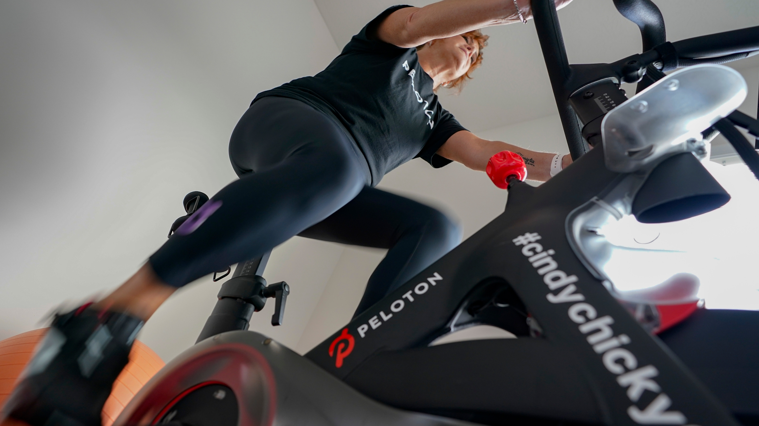 In this photo made on Sunday, Aug. 8, 2021, Cindy Cicchinelli uses her Peloton exercise machine in the workout room of her Pittsburgh townhouse. Cicchinelli says she has become a dedicated Peloton user after going to her gym in Pittsburgh for years, she said the convenience is what has sold her. The pandemic is reshaping America's fitness industry and ushering in a new era of home workouts and virtual classes. High-end exercise equipment maker Peloton is breaking ground Monday, Aug. 9, 2021, on its first U.S. factory in Ohio. (AP Photo/Keith Srakocic)