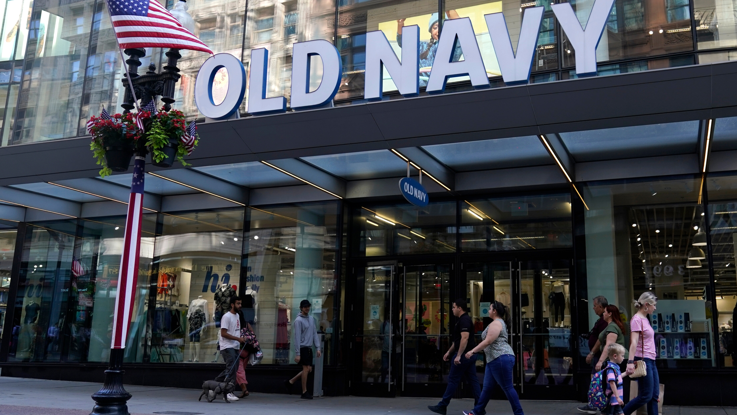 Pedestrians pass the Old Navy store in the Downtown Crossing shopping area, Wednesday, July 14, 2021, in Boston. Gap's low-price division Old Navy is overhauling its approach to how it designs and markets to plus-size women, a growing demographic that many analysts say has been underserved. Starting Friday, Aug. 20, Old Navy will be offering every one of its women's styles in all sizes with no price difference. (AP Photo/Charles Krupa)