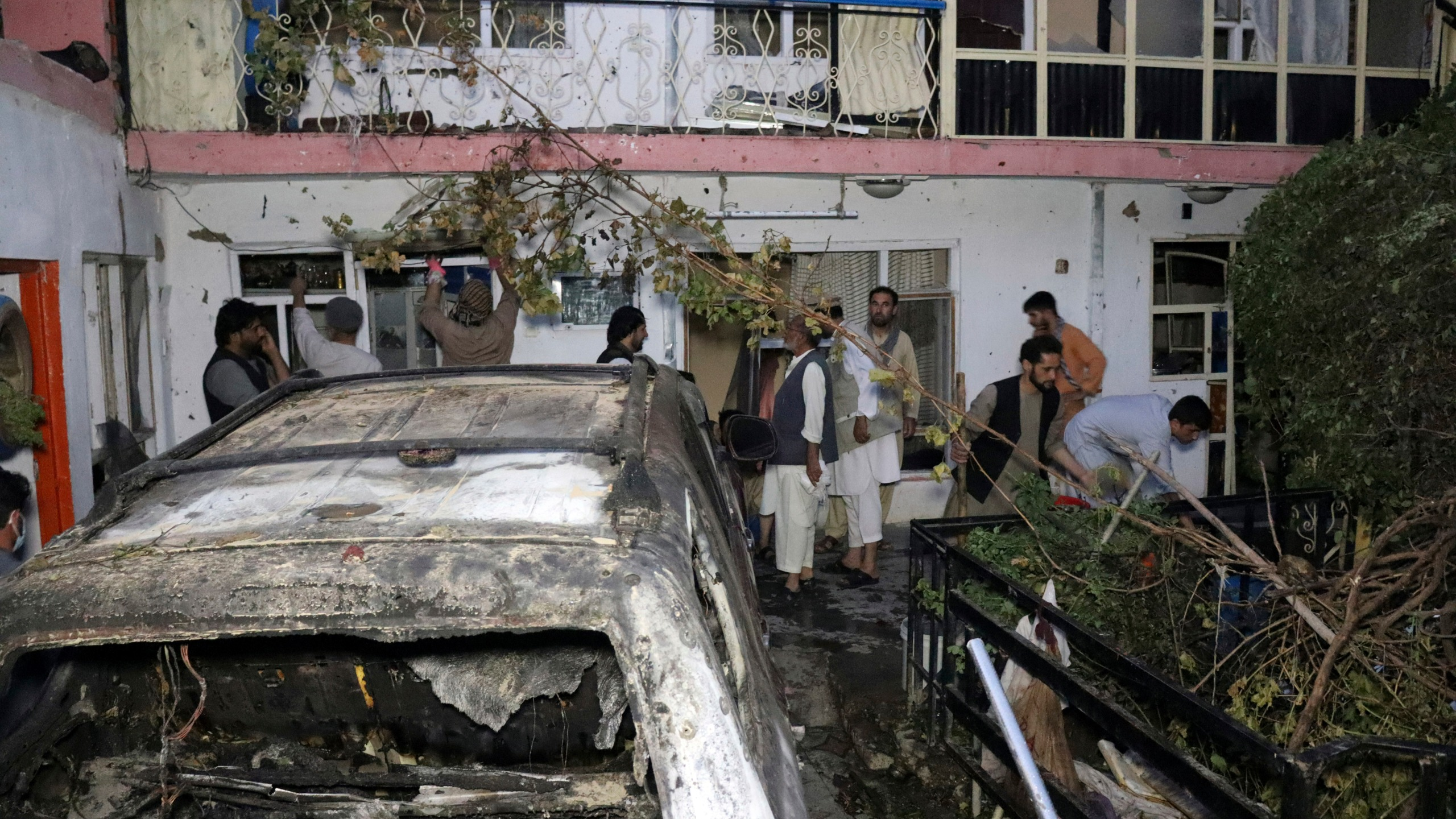 """Afghan people are seen inside a house after U.S. drone strike in Kabul, Afghanistan, Sunday, Aug. 29, 2021. A U.S. drone strike destroyed a vehicle carrying """"multiple suicide bombers"""" from Afghanistan's Islamic State affiliate on Sunday before they could attack the ongoing military evacuation at Kabul's international airport, American officials said. (AP Photo/Khwaja Tawfiq Sediqi)"""