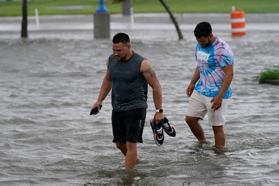 Jesse Perez, center, and Sergio Hijuelo walk through flooded streets near Lake Pontchartrain as Hurricane Ida nears, Sunday, Aug. 29, 2021, in New Orleans. (AP Photo/Gerald Herbert)