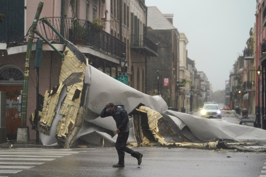 A man passes by a section of roof that was blown off of a building in the French Quarter by Hurricane Ida winds, Sunday, Aug. 29, 2021, in New Orleans. (AP Photo/Eric Gay)