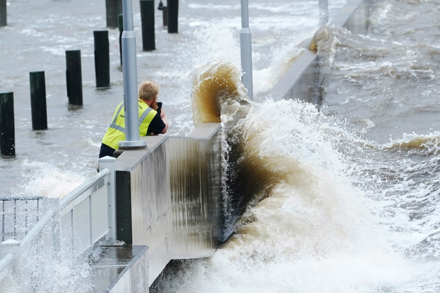 A utility worker photographs waves as they slam against a sea wall at the city marina as outer bands of Hurricane Ida arrive Sunday, Aug. 29, 2021, in Bay Saint Louis, Miss. (AP Photo/Steve Helber)