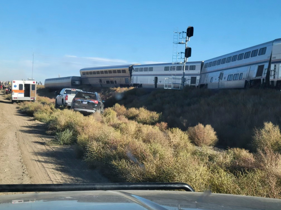 In this photo provided by Kimberly Fossen an ambulance is parked at the scene of an Amtrak train derailment on Saturday, Sept. 25, 2021, in north-central Montana. Multiple people were injured when the train that runs between Seattle and Chicago derailed Saturday, the train agency said. (Kimberly Fossen via AP)