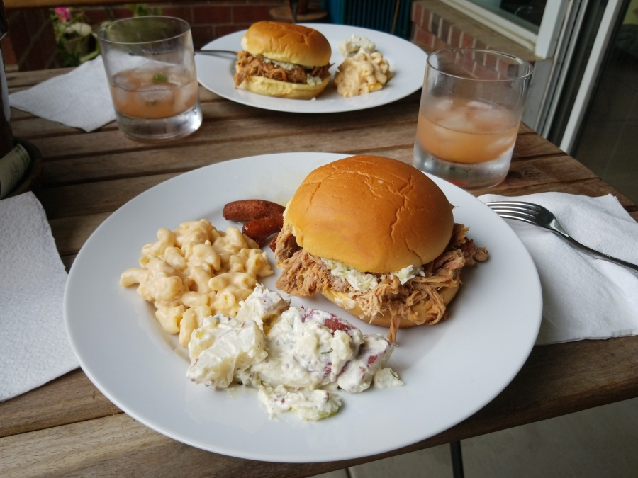A plate with eastern North Carolina style pulled pork BBQ, mac and cheese, potato salad, and hushpuppies (Getty Images)