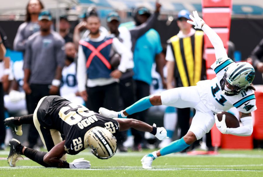 CHARLOTTE, NORTH CAROLINA - SEPTEMBER 19: Wide receiver Robby Anderson #11 of the Carolina Panthers is tackled by cornerback Paulson Adebo #29 of the New Orleans Saints after a catch during the first half at Bank of America Stadium on September 19, 2021 in Charlotte, North Carolina. (Photo by Grant Halverson/Getty Images)
