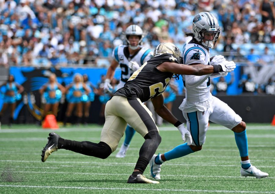 CHARLOTTE, NORTH CAROLINA - SEPTEMBER 19: Wide receiver Robby Anderson #11 of the Carolina Panthers looks to avoid a tackle by cornerback Paulson Adebo #29 of the New Orleans Saints at Bank of America Stadium on September 19, 2021 in Charlotte, North Carolina. (Photo by Mike Comer/Getty Images)