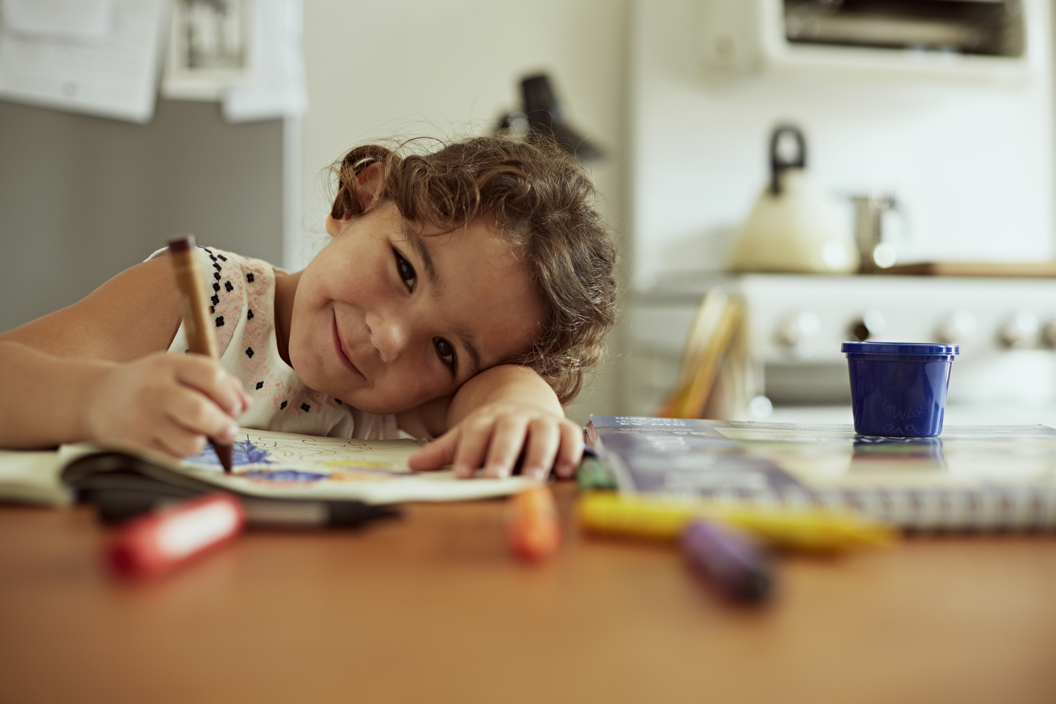 Girl with crayons drawing (Getty Images)
