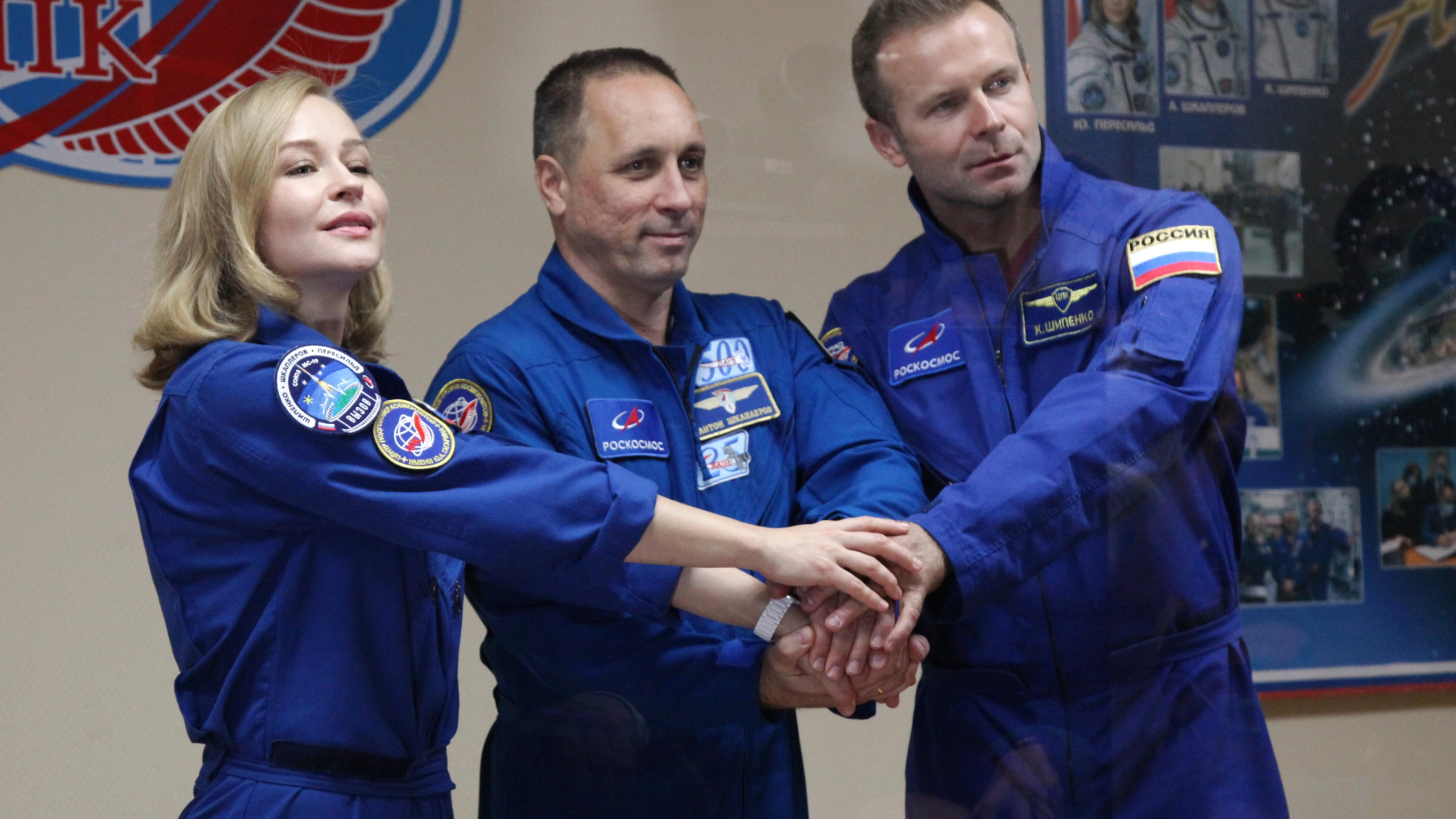 In this handout photo released by Roscosmos, actress Yulia Peresild, left, director Klim Shipenko, right, and cosmonaut Anton Shkaplerov, members of the prime crew of Soyuz MS-19 spaceship pose after a news conference at the Russian launch facility in the Baikonur Cosmodrome, Kazakhstan, Monday, Oct. 4, 2021. In a historic first, Russia is set to launch an actress and a film director to space to make a feature film in orbit. Actress Yulia Peresild and director Klim Shipenko are set to blast off Tuesday for the International Space Station in a Russian Soyuz spacecraft together with Anton Shkaplerov, a veteran of three space missions.(Roscosmos Space Agency via AP)