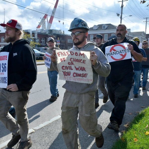 Justin Paetow, center, a tin shop worker at Bath Iron Works, takes part in a demonstration against COVID-19 vaccine mandate outside the shipyard on Friday, Oct. 22, 2021, in Bath, Maine. Some American workers are making the painful decision to quit their jobs and abandon cherished careers in defiance of what they consider intrusive vaccine mandates requiring all businesses with 100 or more workers be fully vaccinated against COVID-19. (AP Photo/Josh Reynolds)